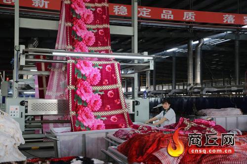 夏邑县印染产业园内工人在印染生产线上赶制订单